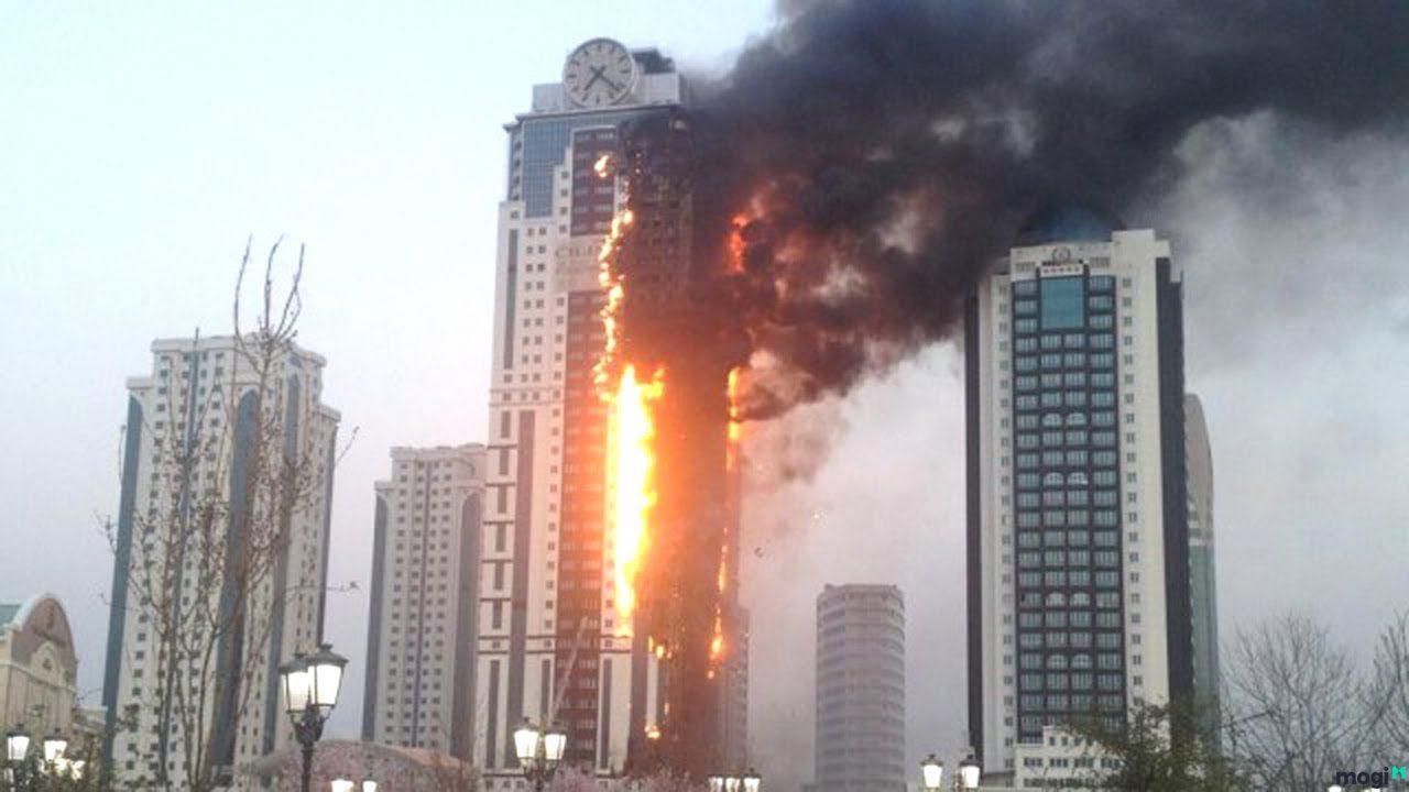 một bàn tay cầm mô hình ngôi nhà, xung quanh có ngọn lửa