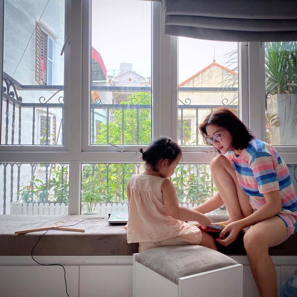 Mẹ và con gái ngồi bên khung cửa sổ phòng ngủ