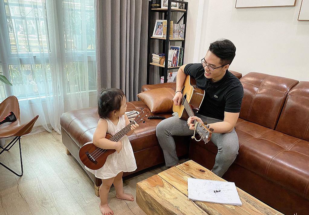 Bố và con gái ngồi chơi đàn