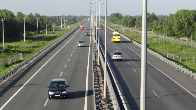 cao tốc 2 làn xe có nhiều ô tô đang chạy, hai bên đường có nhiều cây cối