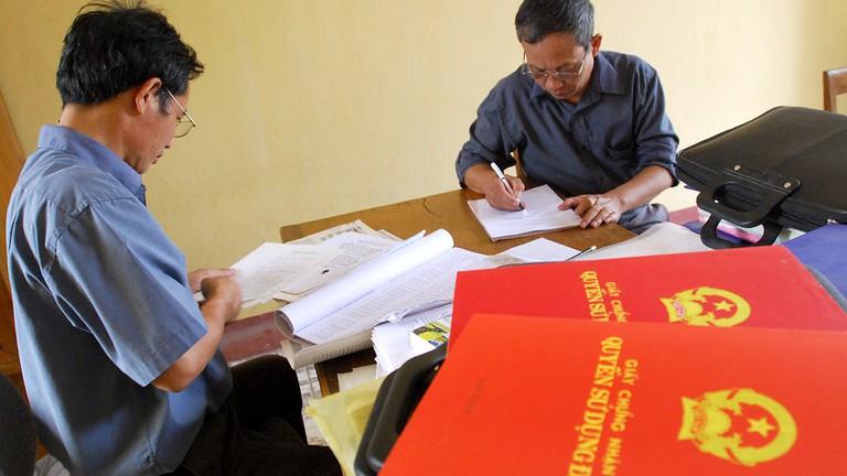 3 người đang ngồi xem xét các giấy tờ, bên cạnh là 3 cuốn sổ đỏ