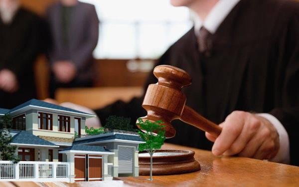 một thẩm phán đang ngồi xét xử tại toa, bên cạnh là mô hình ngôi nhà