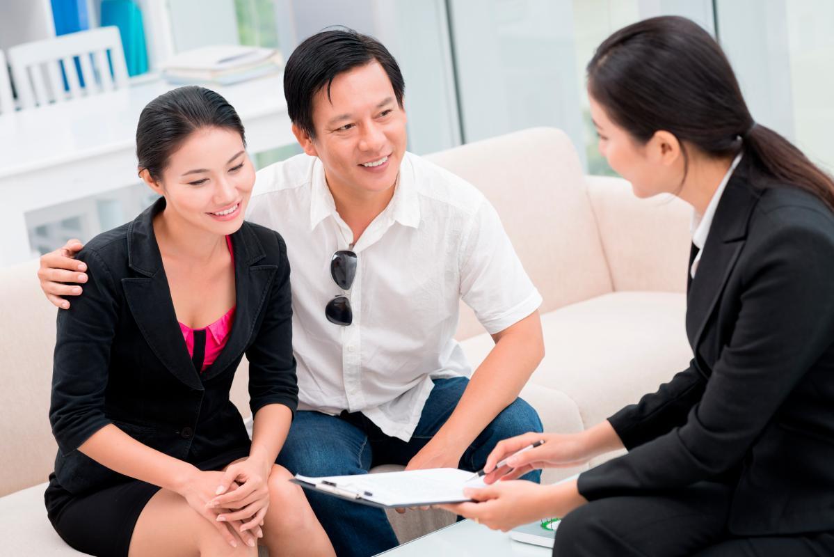 môi giới bất động sản nữ đang ngồi tư vấn cho hai vợ chồng