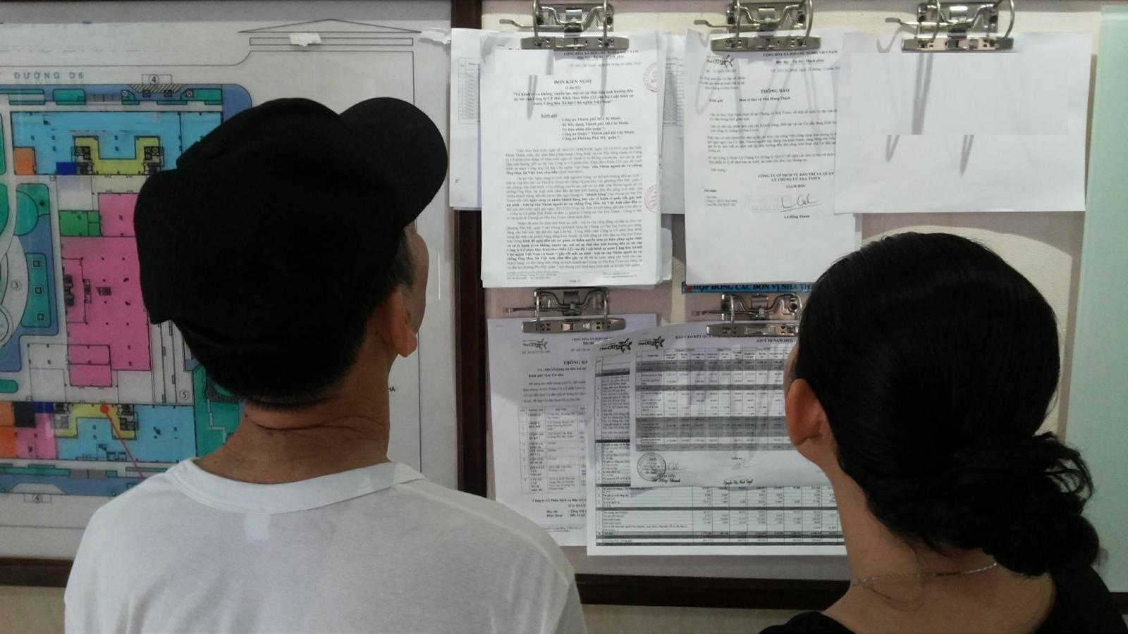người dân đọc bảng tin về cưỡng chế thu hồi đất