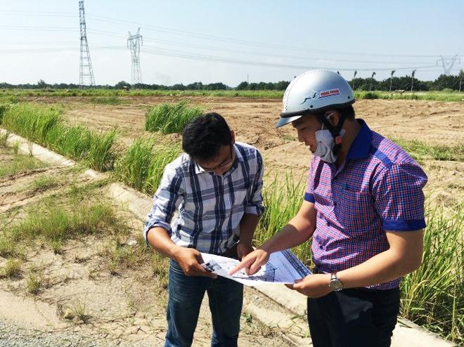 2 người đang xem bản đồ một khu đất trống