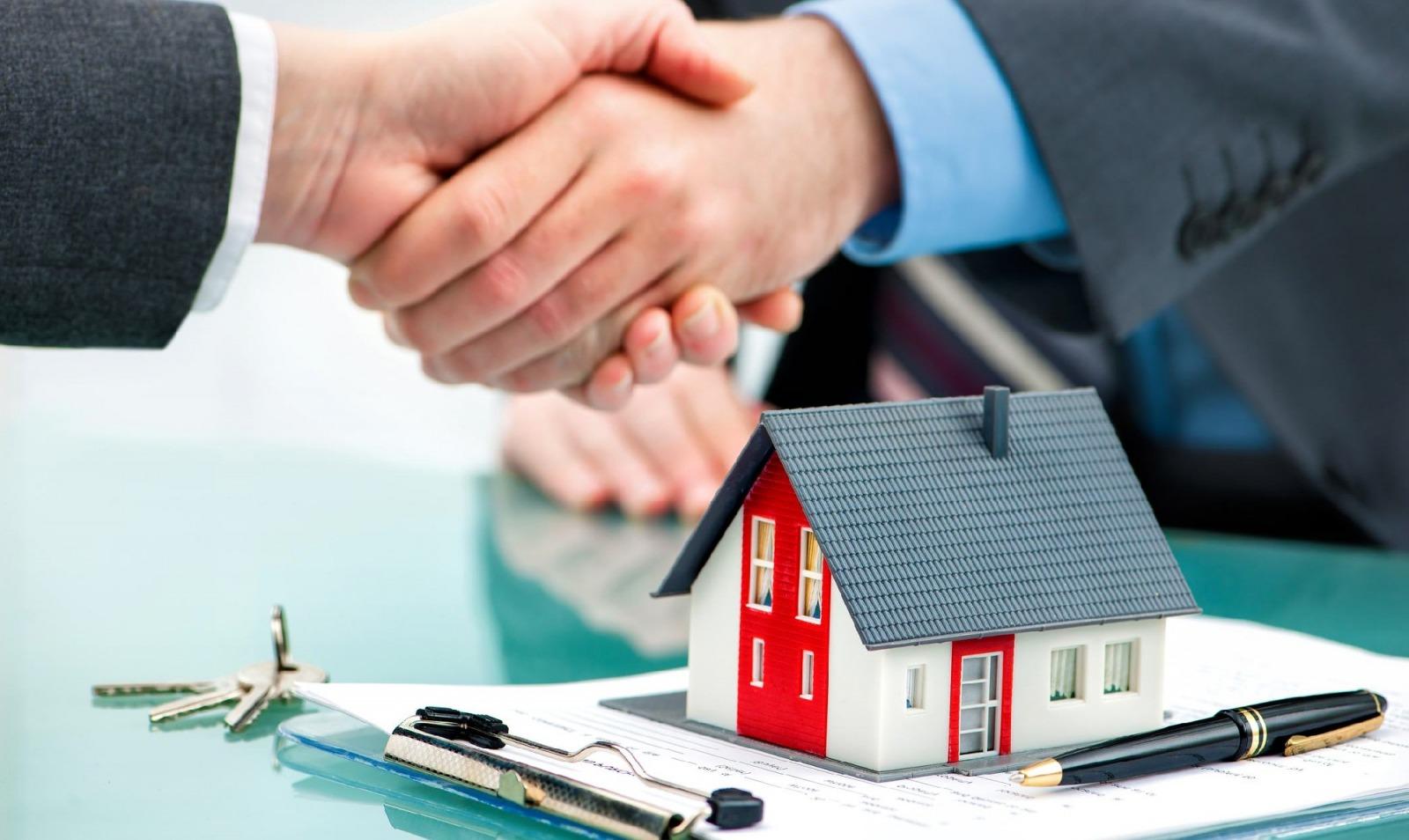 hai người bắt tay nhau, trên bàn là một tờ hợp đồng và một mô hình ngôi nhà