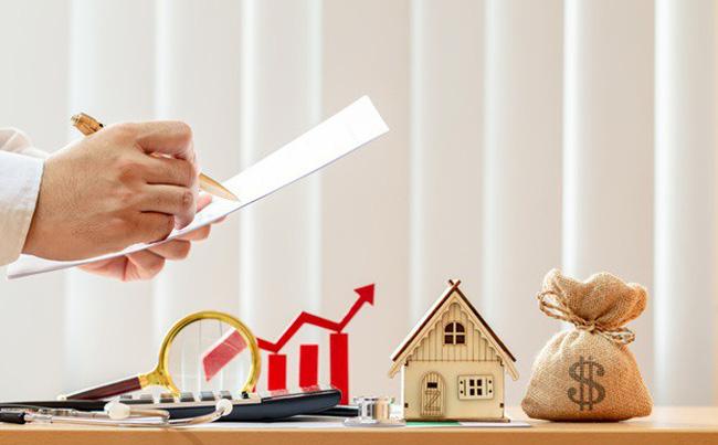 một người đang tính toán các con số, bên cạnh là mô hình ngôi nhà và túi tiền