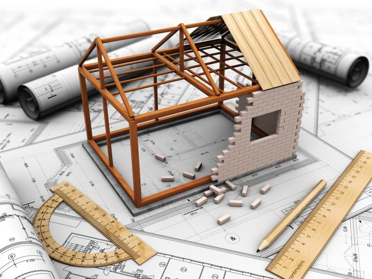 mô hình ngôi nhà đang lắp ghép dở, xung quanh là các loại giấy tờ, hợp đồng