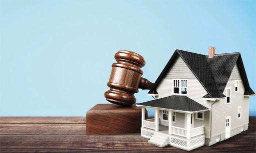 mô hình ngôi nhà được đặt bên trên cuốn sách luật
