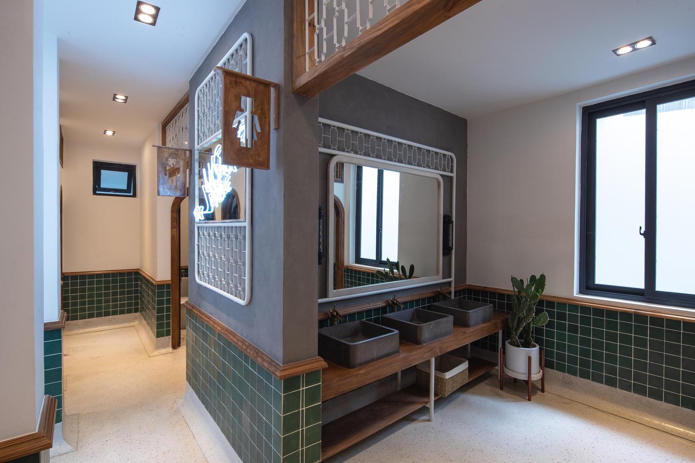 Khu vệ sinh với tường ốp gạch tông màu xanh nhẹ nhàng, trang nhã.