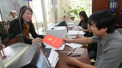 hình ảnh trong văn phòng đăng ký đất đai, 2 người đang trao và nhận cuốn sổ đỏ