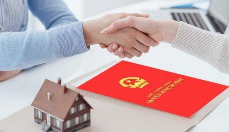 hai người đang bắt tay nhau, trên bàn là cuốn sổ đỏ nhà đất