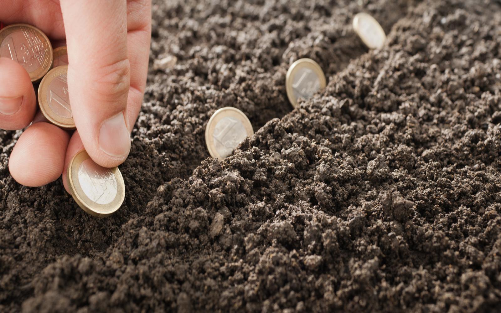 một người đang rải những đồng xu xuống đất