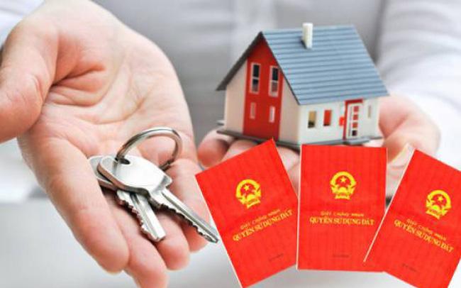 một bàn tay cầm chìa khóa nhà, một bàn tay cầm mô hình ngôi nhà, bên cạnh là cuốn sổ đỏ