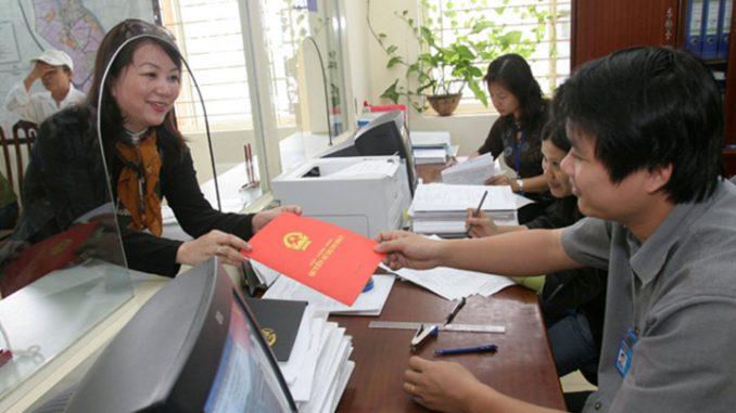 người dân ngồi làm thủ tục trong văn phòng đăng ký đất đai