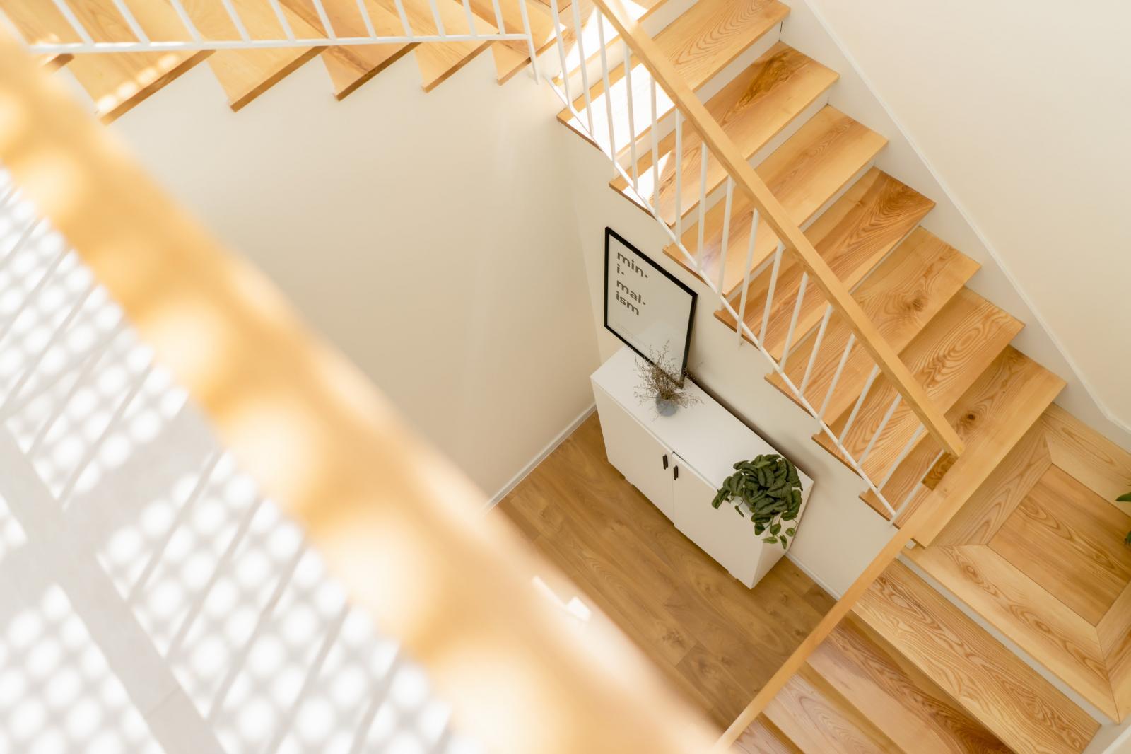 Cầu thang bằng gỗ sáng màu kết nối 2 tầng nhà.