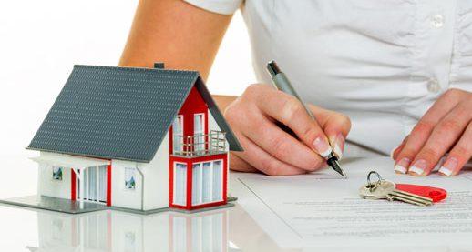 một người đang ngồi viết, trên bàn có 1 mô hình ngôi nhà