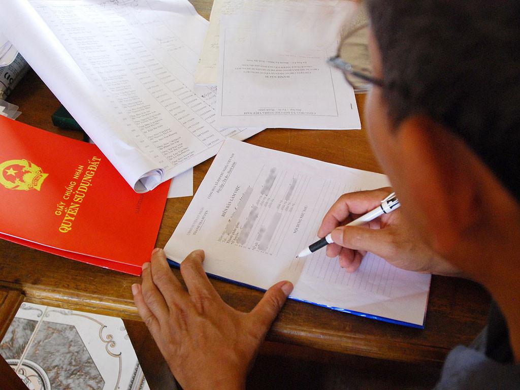 một bàn tay cầm cuốn sổ hồng, trên bàn là nhiều giấy tờ đất đai khác