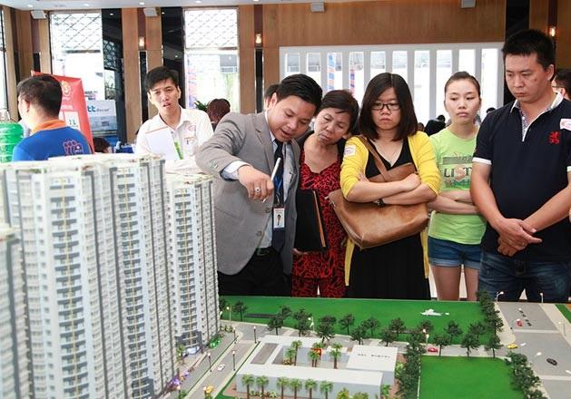 môi giới đang giới thiệu về khu chung cư thông qua mô hình cho khách hàng