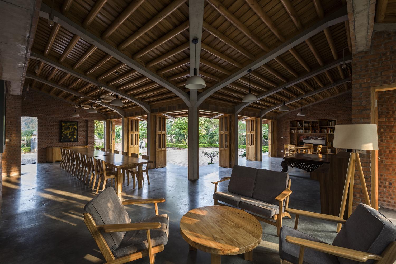 Đồ nội thất bằng gỗ xoan, tường gạch mộc truyền thống và sàn bê tông hiện đại kết hợp hài hòa