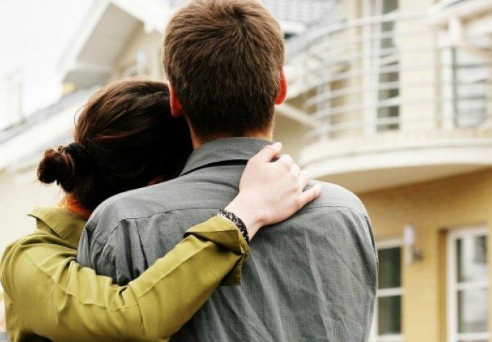 hai vợ chồng đang cùng nhìn về phía ngôi nhà