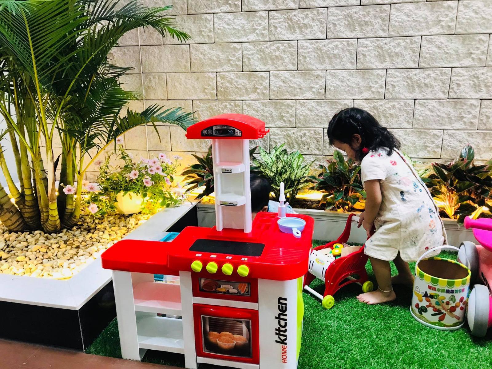 Bé gái vui chơi trong căn bếp đồ chơi được bố trí ở khu vực giếng trời.