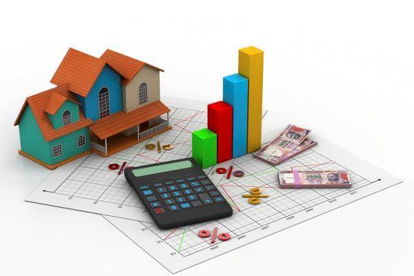 mô hình ngôi nhà, bên cạnh là giấy tờ, tập tiền và chiếc máy tính