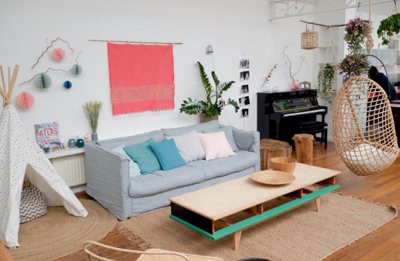 Màu hồng và xanh pastel thêm sức sống cho không gian phòng khách Scandinavia có  tường trắng và sàn gỗ màu nâu trung tính.