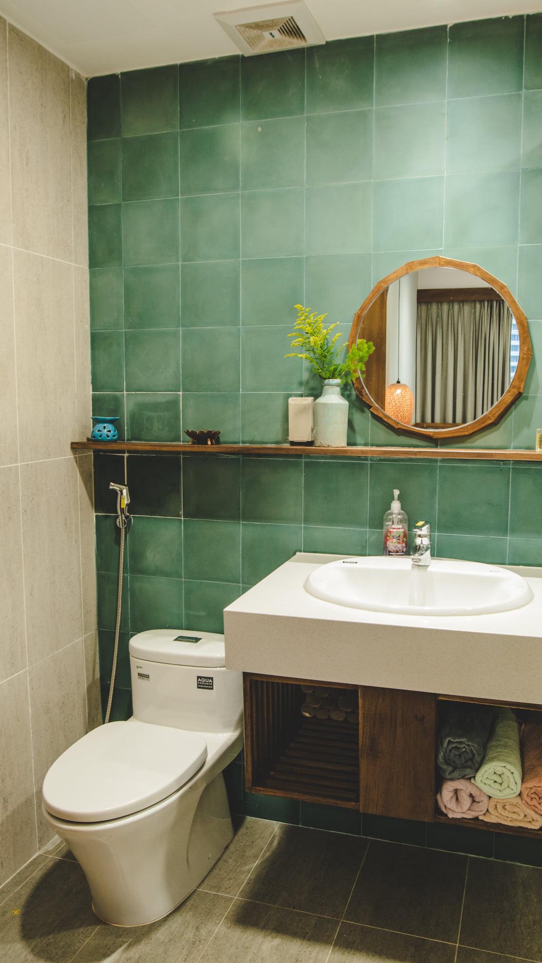 Phòng vệ sinh sử dụng gạch ốp tường tông xanh mát mắt.