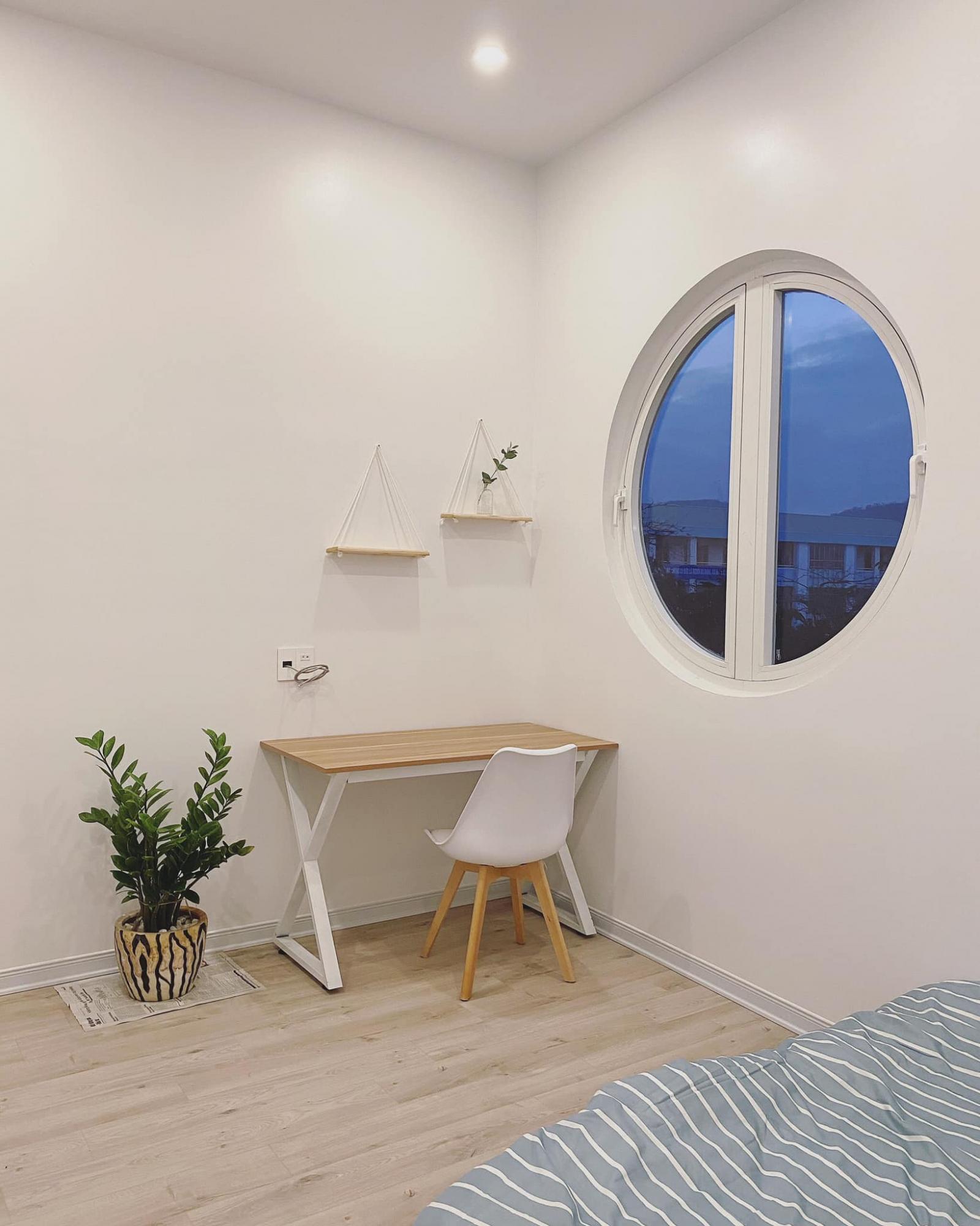 Góc làm việc, học tập được bố trí cạnh cửa sổ khung tròn xinh xắn.