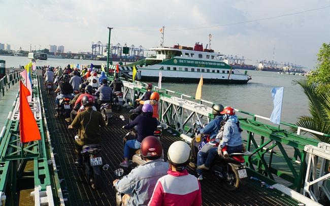 nhiều người và xe máy đang đợi qua phà qua sông