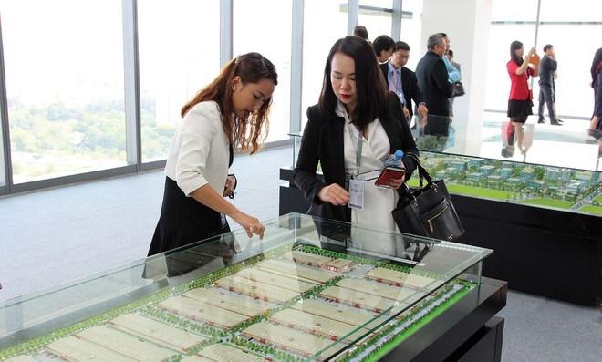 hai người đang đứng trao đổi về mô hình khu đất công nghiệp