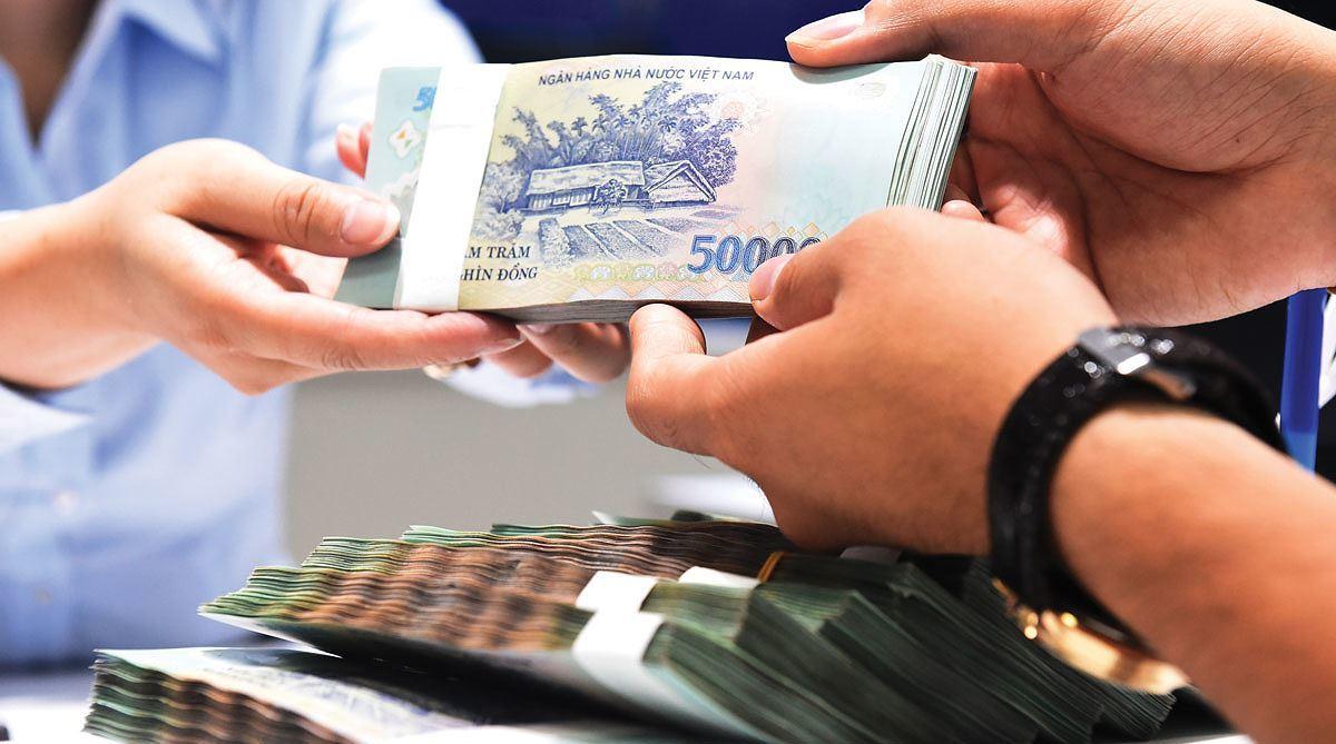 nhân viên ngân hàng đưa tiền cho người vay