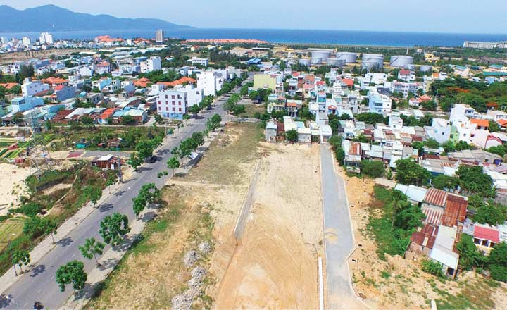 bãi đất trống và nhiều nhà ở, phía xa là biển