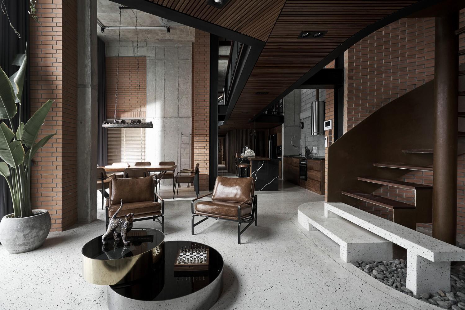 Nội thất sử dụng tông màu trầm ấm, hài hòa với màu xám của trần, cột bê tông xám và sàn gạch sáng màu.