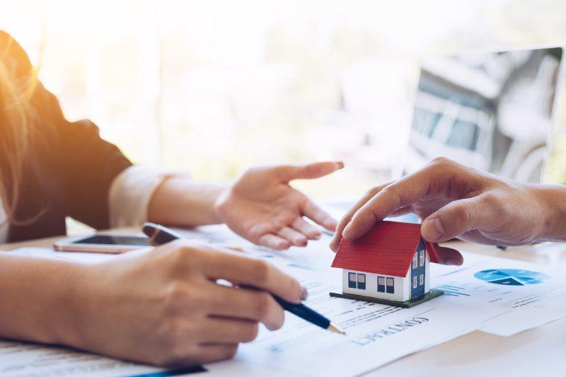 hai bàn tay đang chỉ vào tờ hợp đồng mua bán, bên cạnh là mô hình ngôi nhà