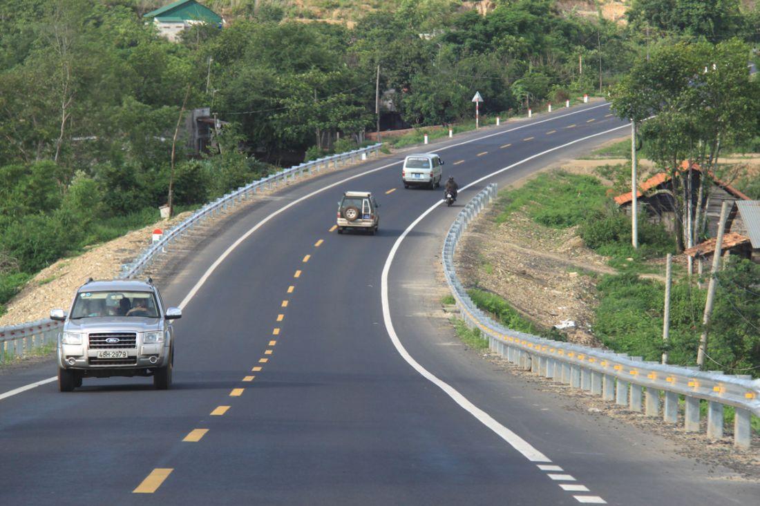cao tốc có xe đang chạy, hai bên đường có nhiều cây cối