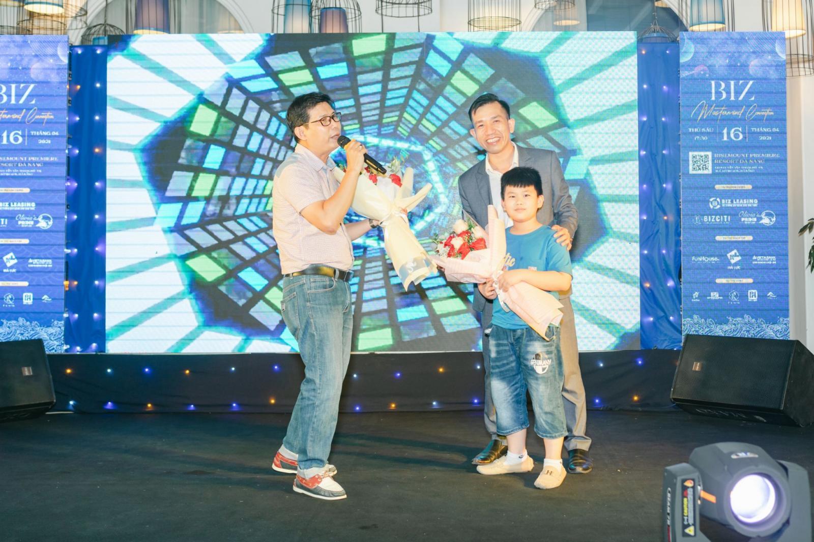 2 người đàn ông và một bé trai đứng trên sân khấu