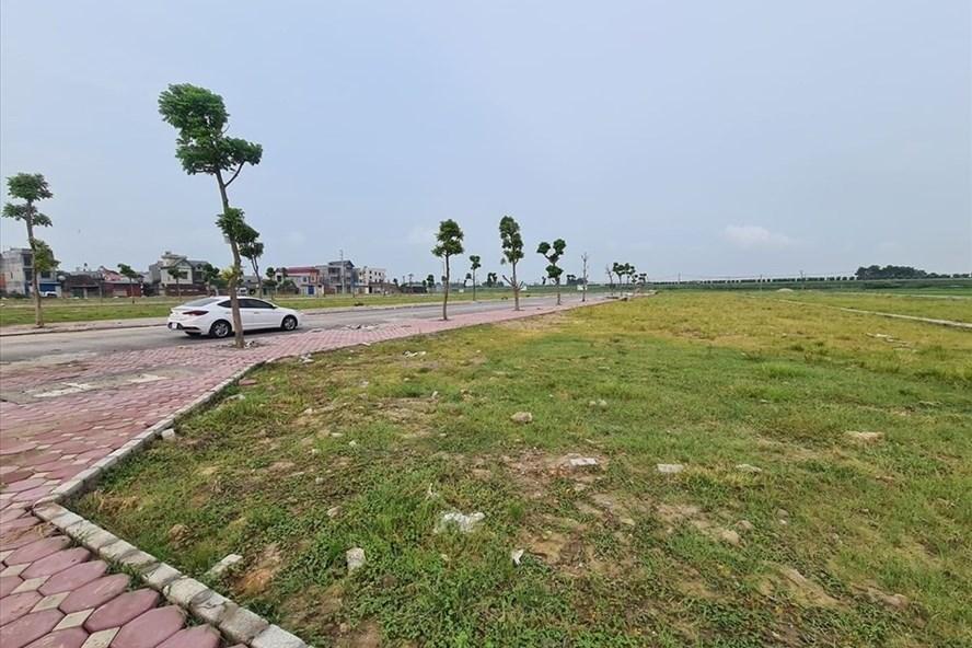 khu đất trống cạnh đường đi có ô tô đang đỗ