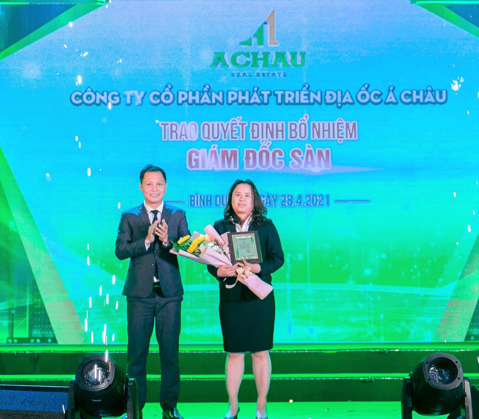 một người đàn ông và một người phụ nữ ôm hoa đứng trên sân khấu