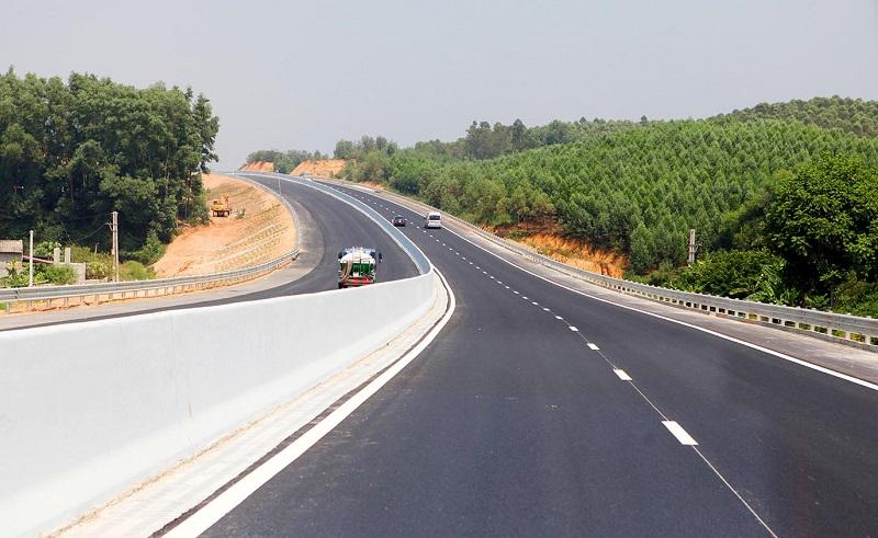 xe đang đi trên đường cao tốc, hai bên có nhiều cây xanh