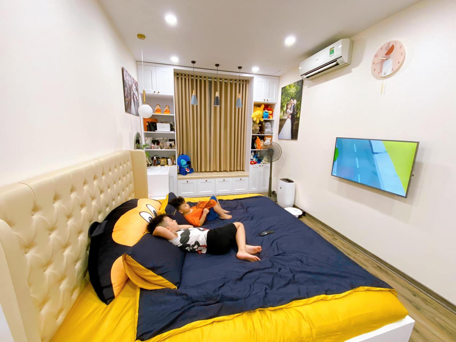hai đứa bé nằm trên giường xem tivi