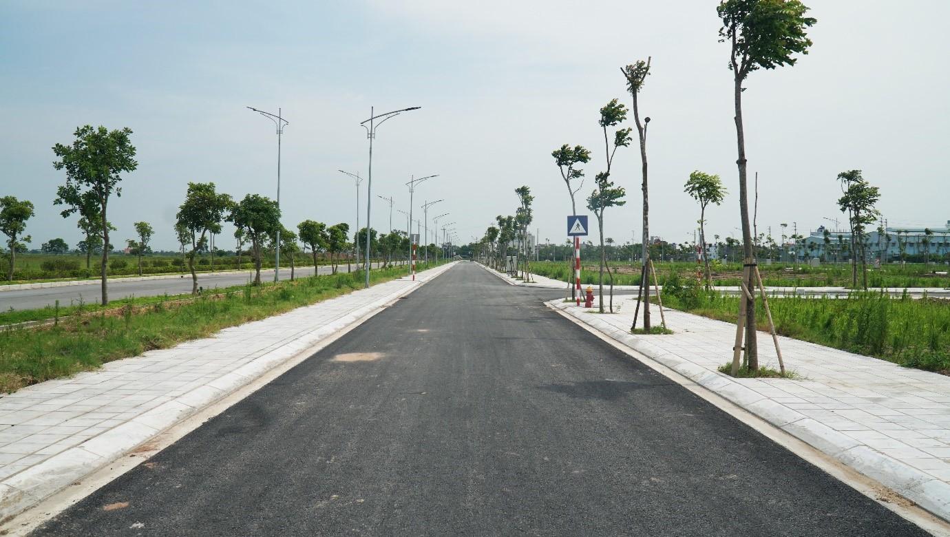 đường đi giữa khu đất trống và cây xanh