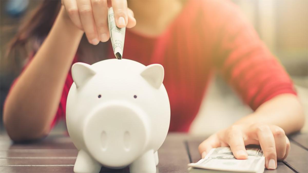 một người đang đút tiền vào lợn minh họa cho việc tiết kiệm tiền