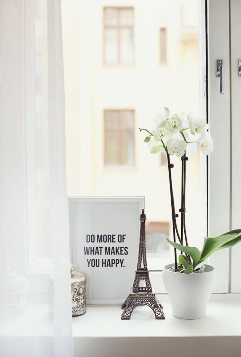 Một góc cửa sổ phòng khách được trang trí bằng cây hoa và đồ vật trang trí nhỏ xinh