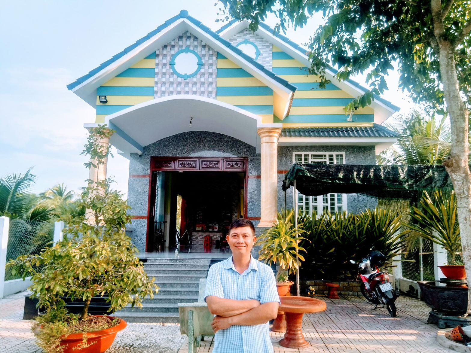 Anh Linh đứng trước ngôi nhà khang trang của mình